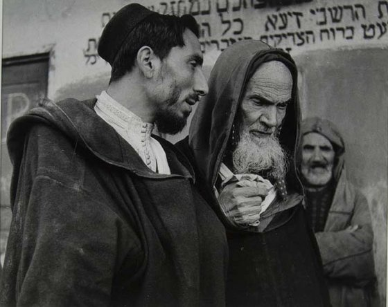 black and white photograph of a younger man speaking with an older man who wears a hooded garment, another man stands in the background in front of a wall with Hebrew writing