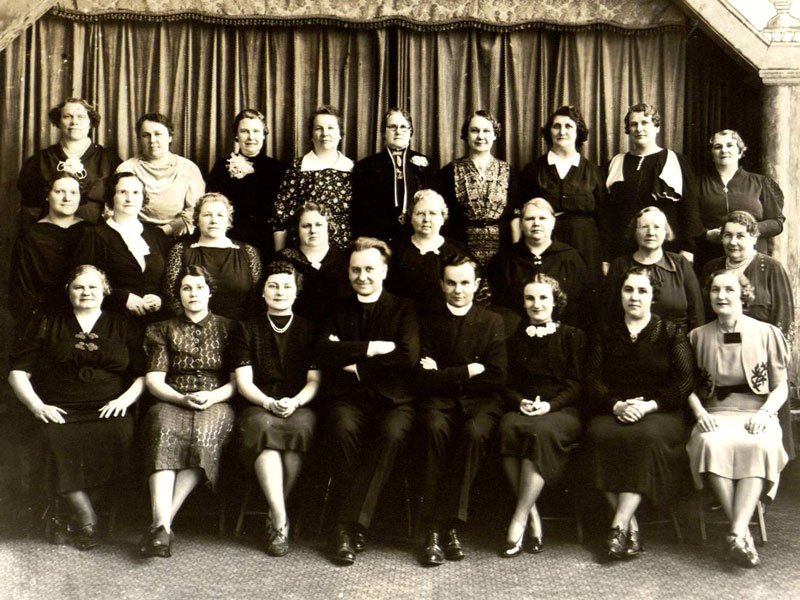 black and white group portrait of a number of women and two priests