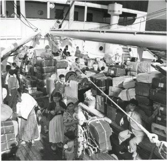 black and white photograph of a group of people among a large amount of suitcases