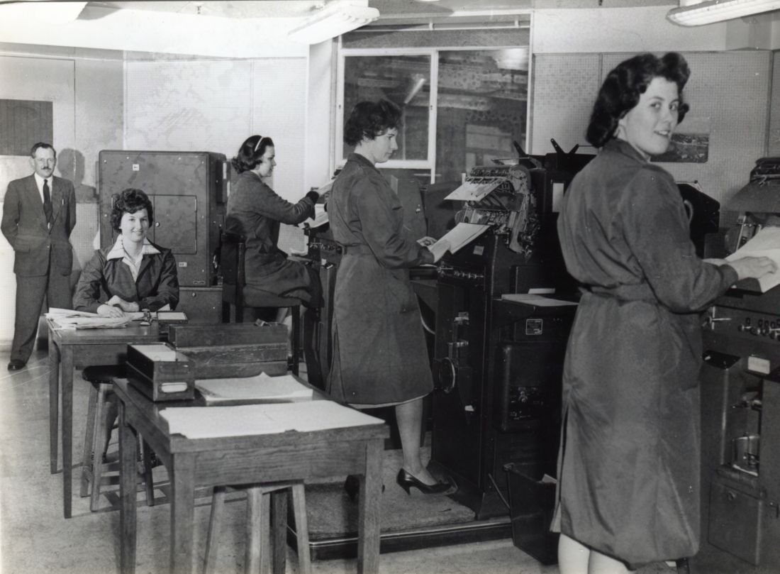black and white photograph of several women in an office, three are standing by machines, one is sitting at a desk, a man is standing in the background