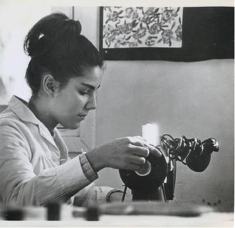black and white photograph of a young woman using a piece of equipment