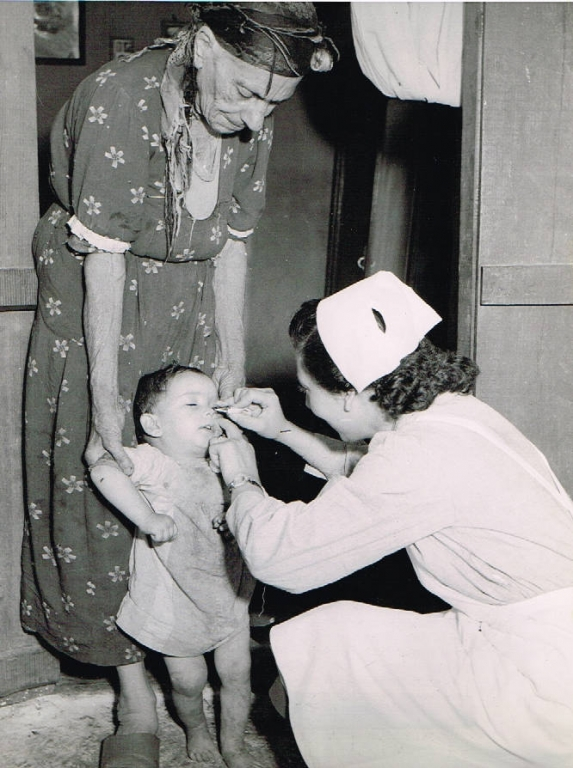 black and white photograph of a nurse treating a child's eye who is being held by an older woman