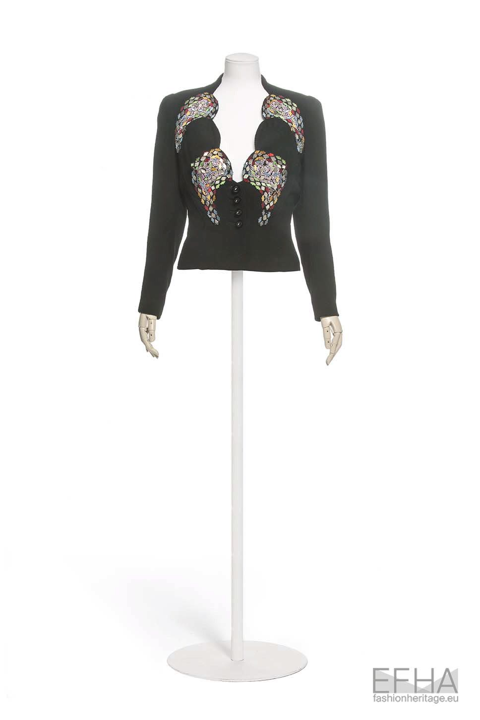 Short black jacket with multicoloured sequins, displayed on a mannequin