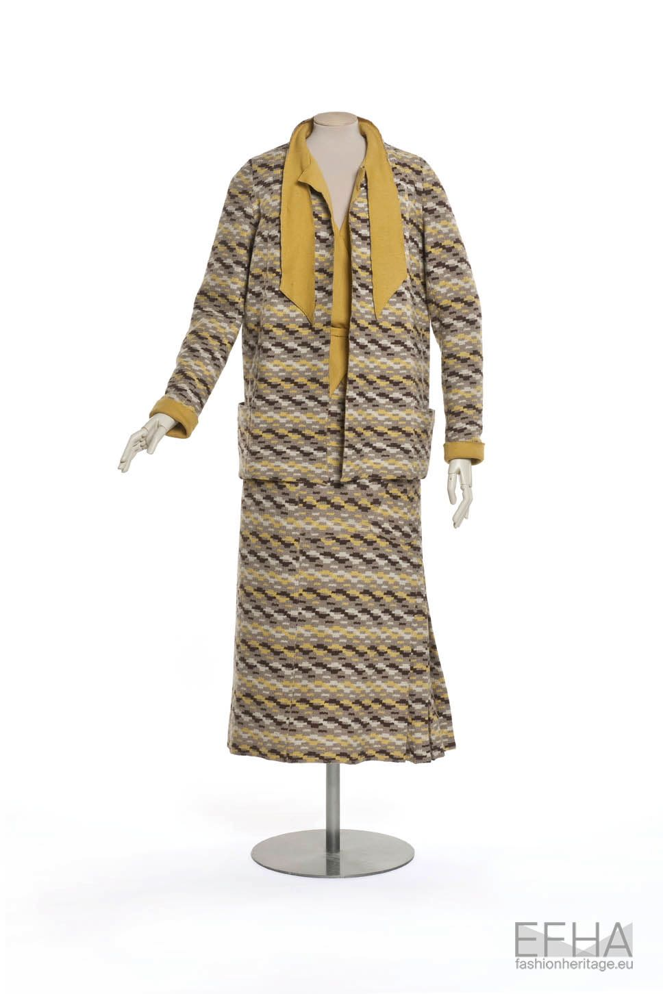 Tailored two-piece suit with skirt in cream, brown and yellow colours, displayed on a mannequin