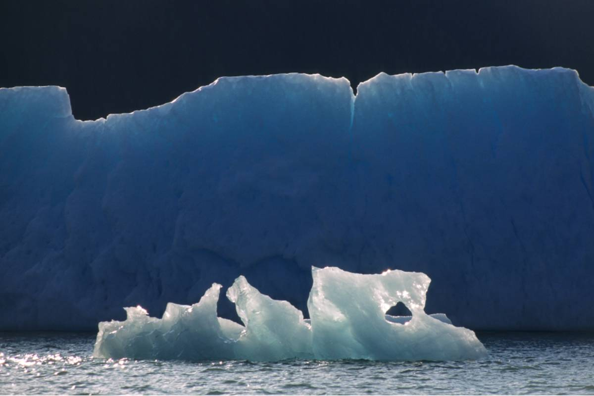 Large iceberg in the background with a smaller ice formation in front of it
