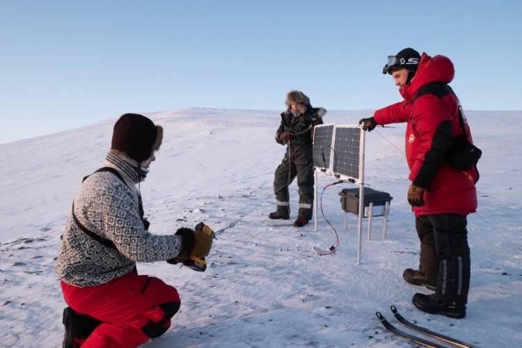 Researchers set up a camera and solar panels near a polar bear den site