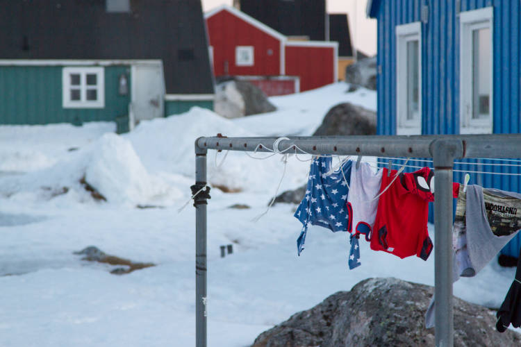 Laundry hanging to dry outside of a home in the arctic, surrounded by snow