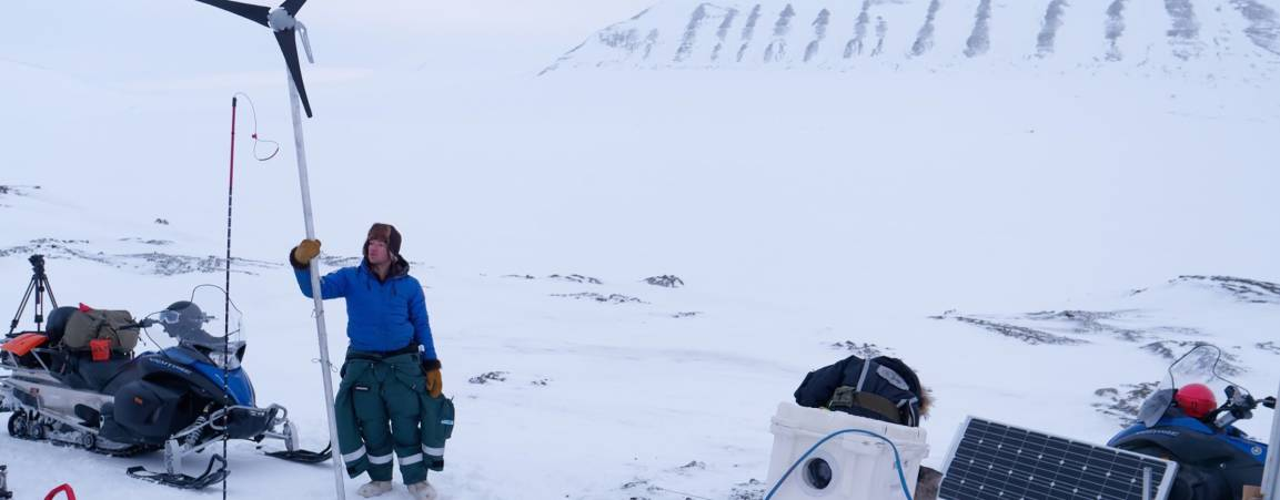 Two researchers looking out towards the tundra while another researcher is setting up equipment