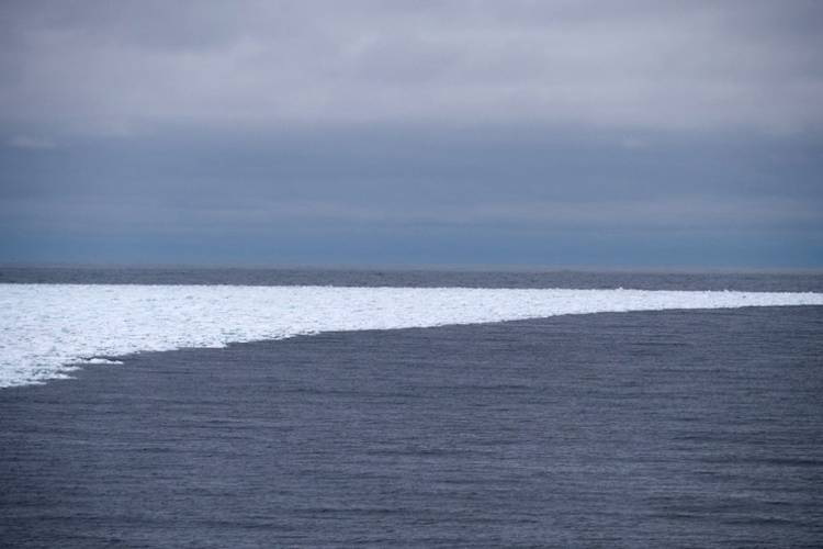 A small band of sea ice curves into open ocean waters.