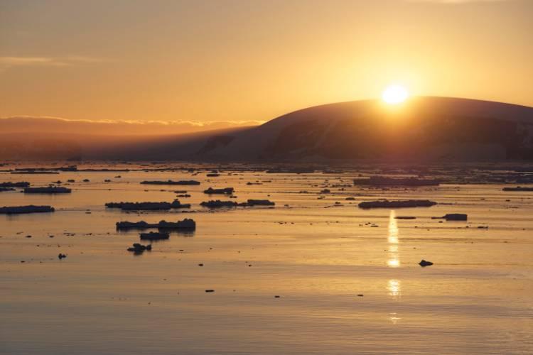 The sun peeking behind a glacier