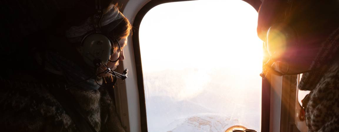 Researchers looking out the window at a vast Arctic landscape