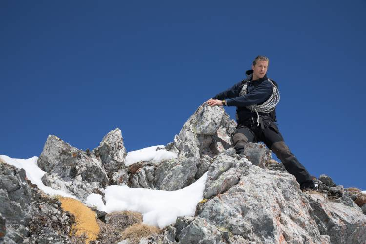 Television host Bear Grylls on a rocky outcropping in the Arctic.