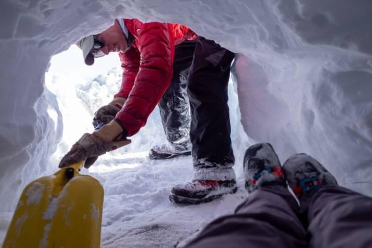 Polar Bears International staff member BJ Kirschhoffer shown excavating an artificial den for the SAR test