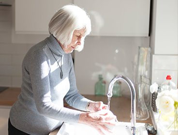 Elderly woman washing dishes in the sink