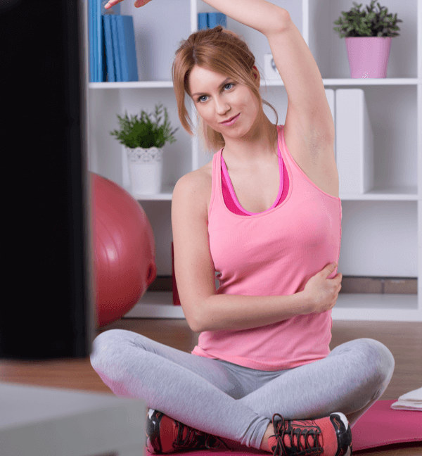 Woman stretching while watching the TELUS Healthy living network on a TV