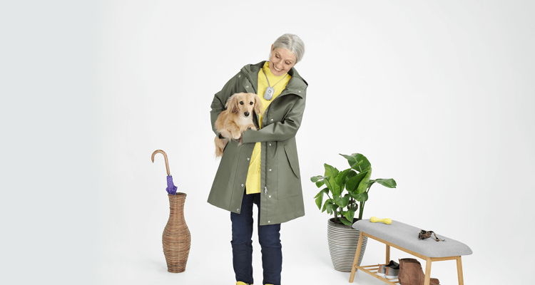 Elderly woman wearing LivingWell Companion Go device while holding her dog