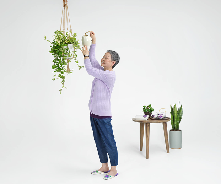 Elderly lady wearing LivingWell Companion Home wristband, watering plants — LivingWell Companion Home base station on nearby table.