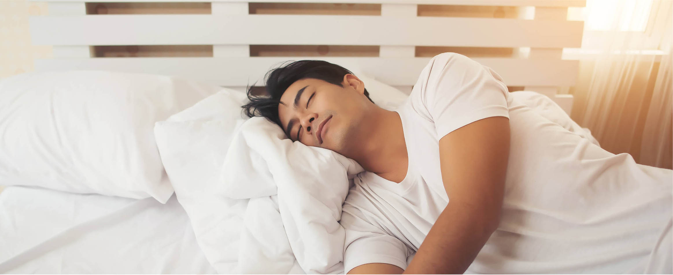A man sleeps comfortably on a soft pillowy bed.