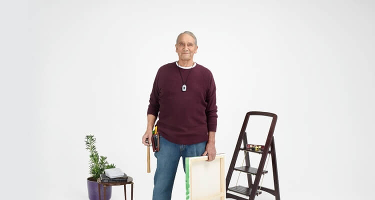 Elderly man wearing LivingWell Companion Go device with a toolbelt