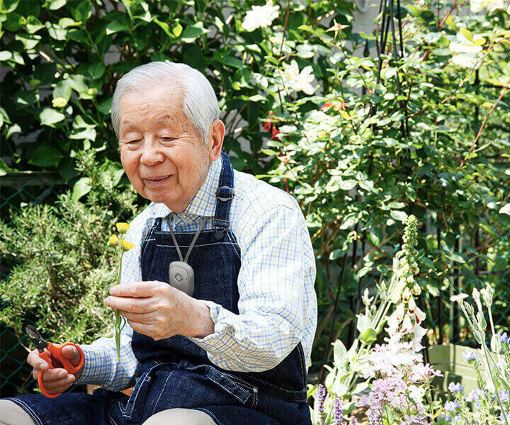 An elderly man gardening outside.