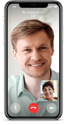 A mobile device showing a smiling woman on a video call with her doctor.