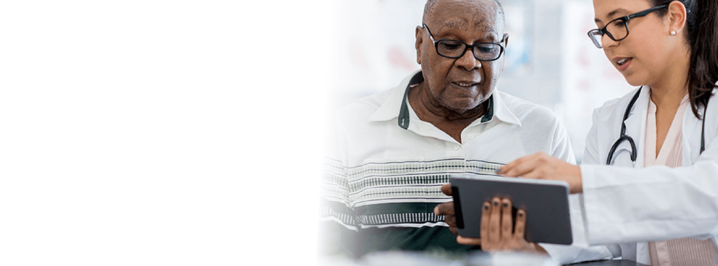 An elderly man sits with his young female doctor, reviewing his Electronic Medical Records on a tablet.