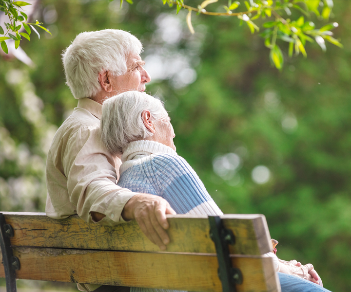 An elderly couple sitting together on a park bench.
