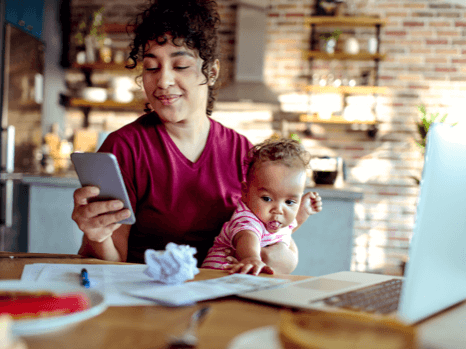A female holding her baby booking an appointment with her doctor using the TELUS Babylon App on a smartphone.