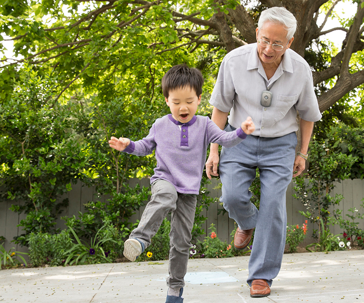 A grandfather playing outside with his grandchild.