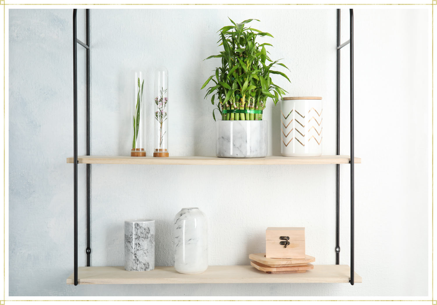 a shelving unit with a marble pot and bamboo inside and a white decorative jar and two dried flowers. The bottom shelf has two glass jars.