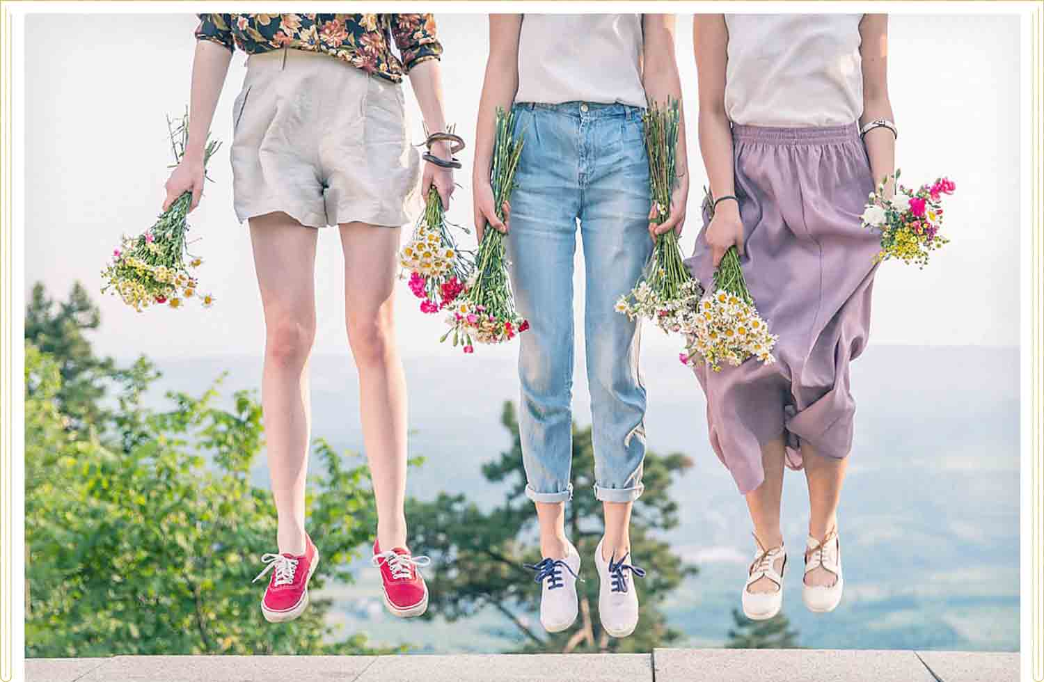three girls holding flowers while jumping