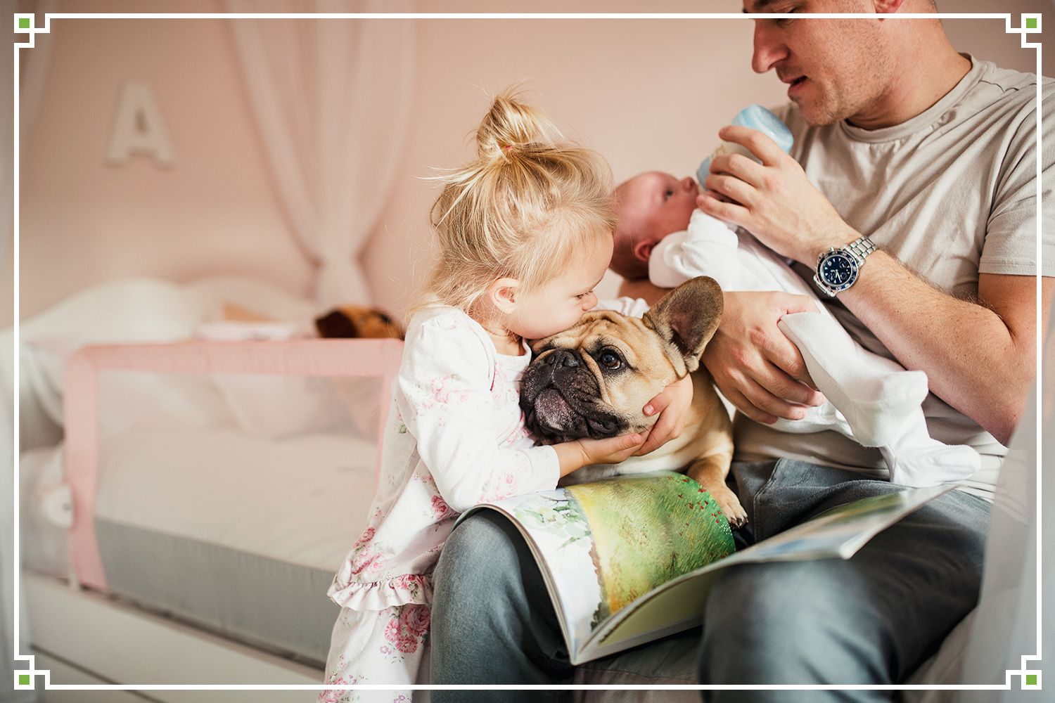 young girl kissing bulldog while dad bottlefeeds baby
