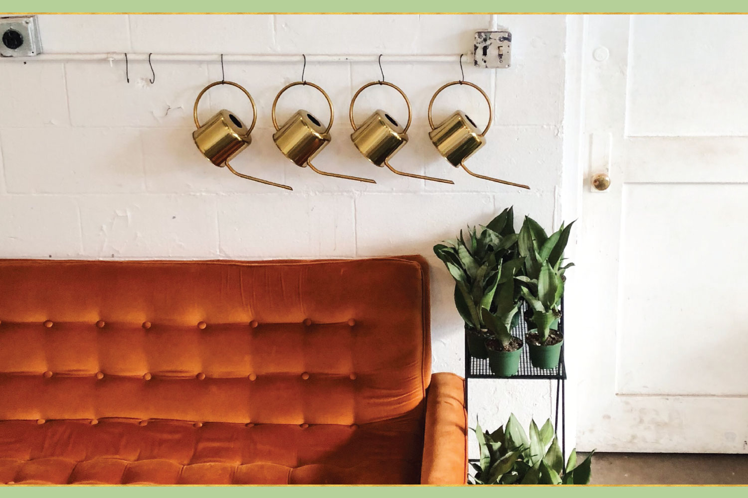 four gold watering cans hanging