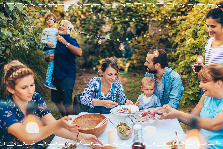 family eating outside under stringlights