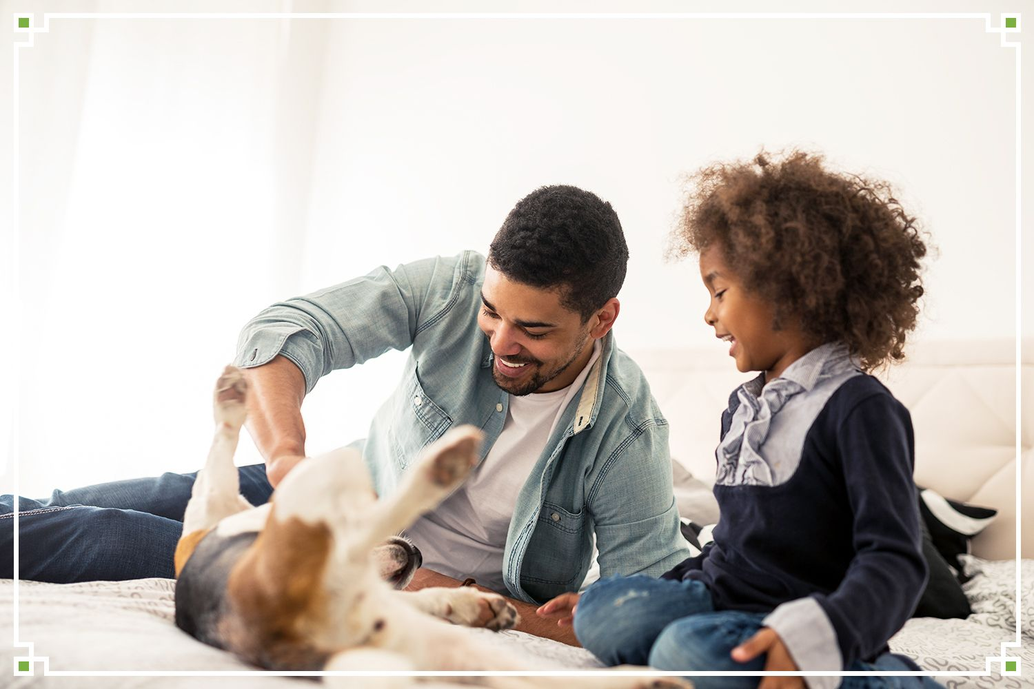 father and child playing with dog on bed