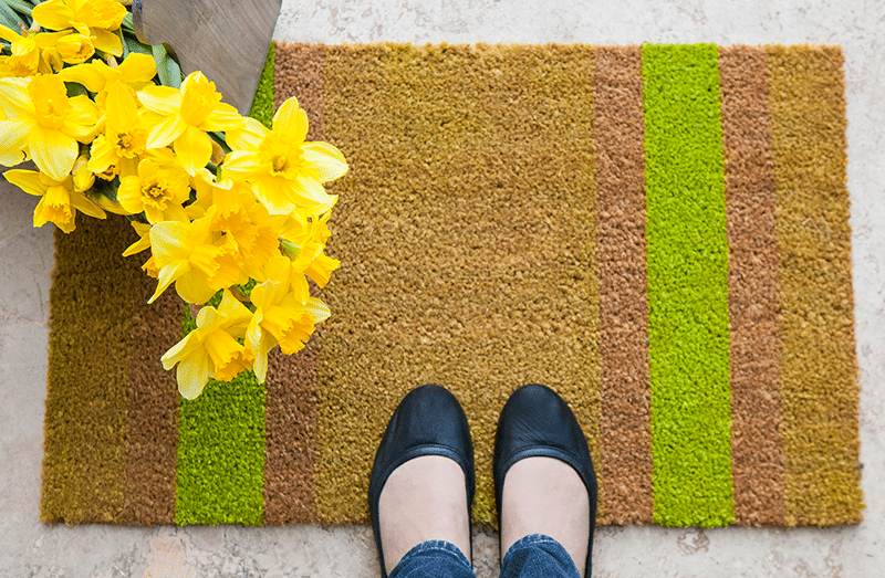 two feet in shoes on a mat with daffodils