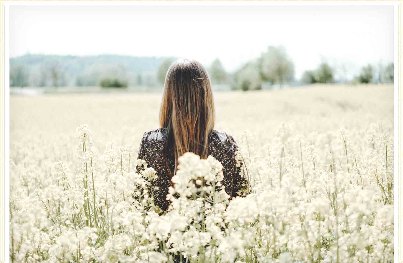 girl walking through field of white flowers