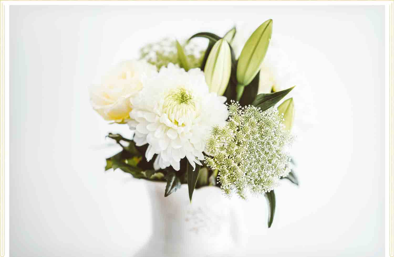 a bouquet of white flowers in a white vase