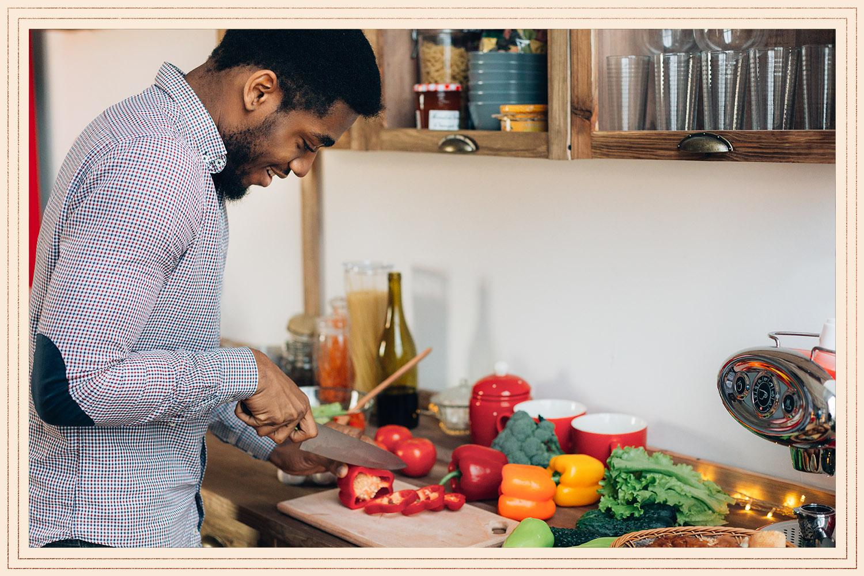 man cutting vegetables in kitchen