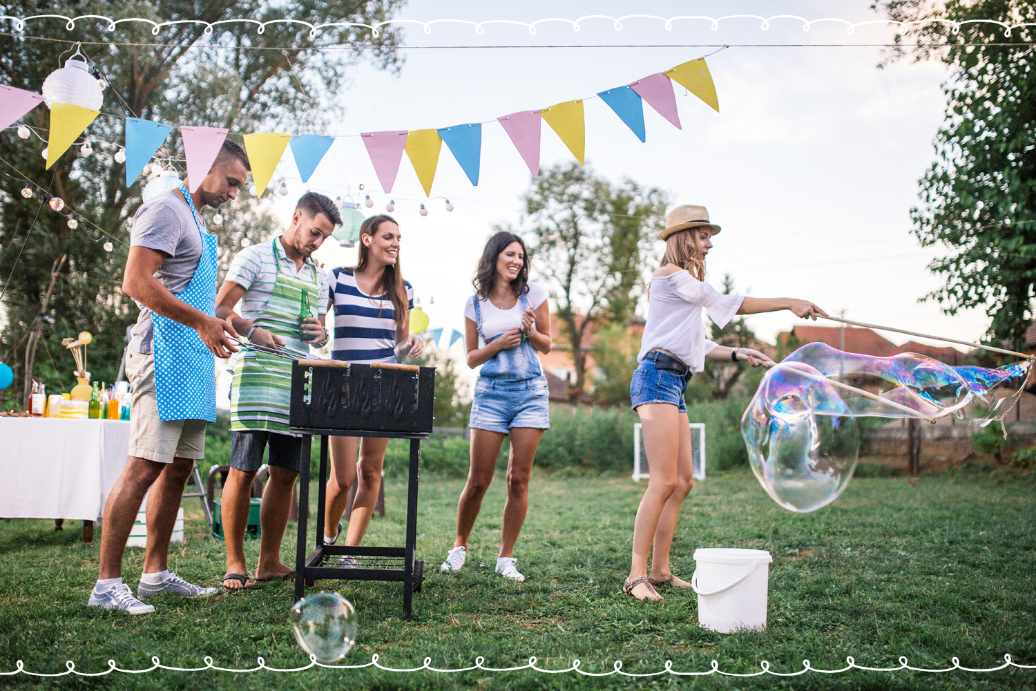 adult friends grilling outside and playing with bubbles