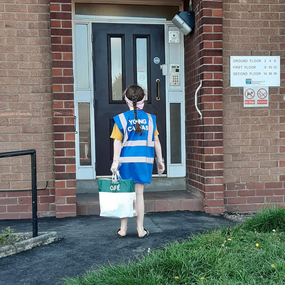 young girl stood at a front door delivering essential items to vulnerable people