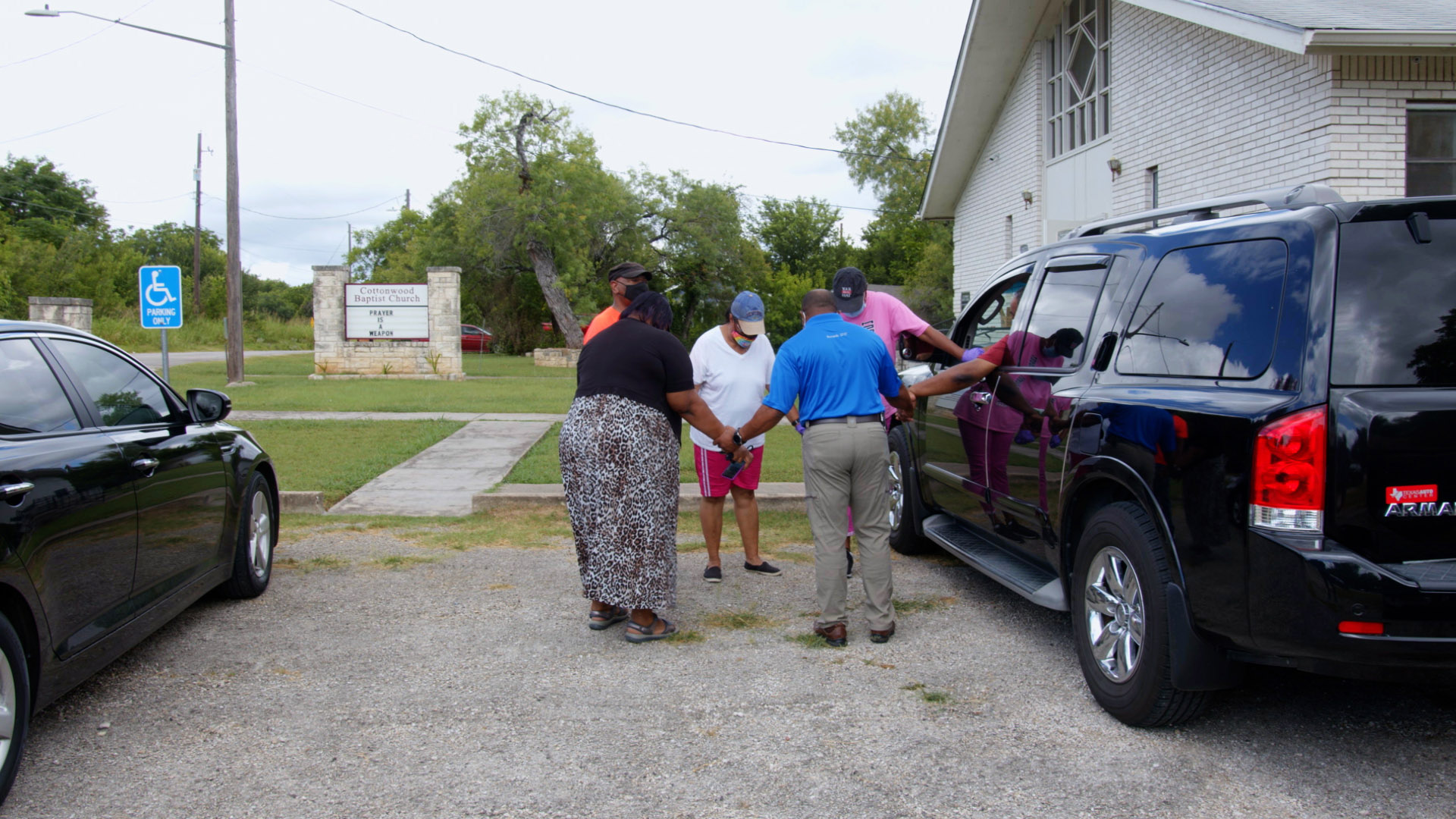 The Rev. Byron K. Jackson leads a prayer before he and volunteers distribute 125 meals to residents facing food insecurity in the neighborhood near Cottonwood Baptist Church on June 29, 2021