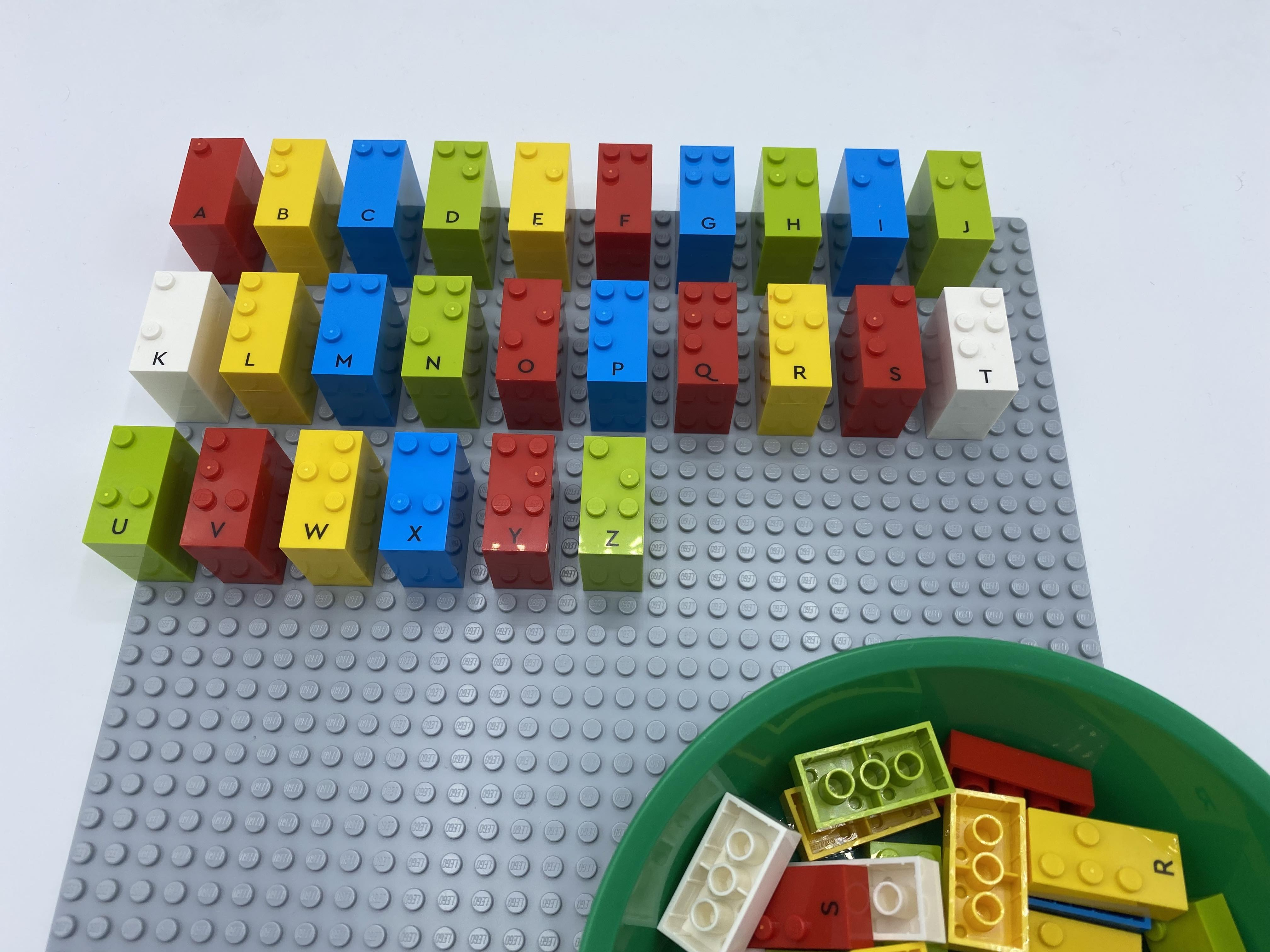 Alphabetical baseplate and a bowl full of LEGO Braille Bricks.