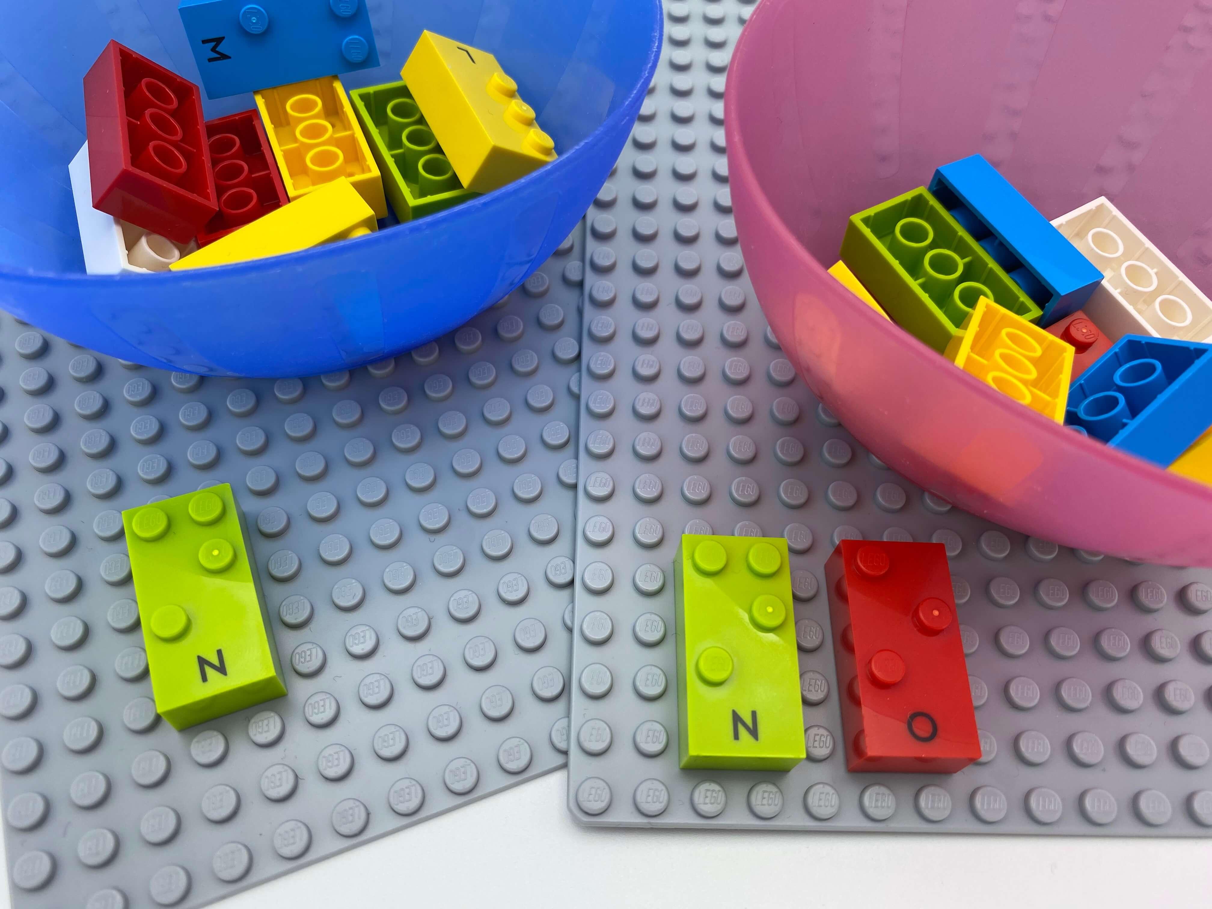 "2 base plates, 2 bowl with bricks. A letter brick n on one base plate, letter bricks ""n"" and ""o"" on the second base plate."