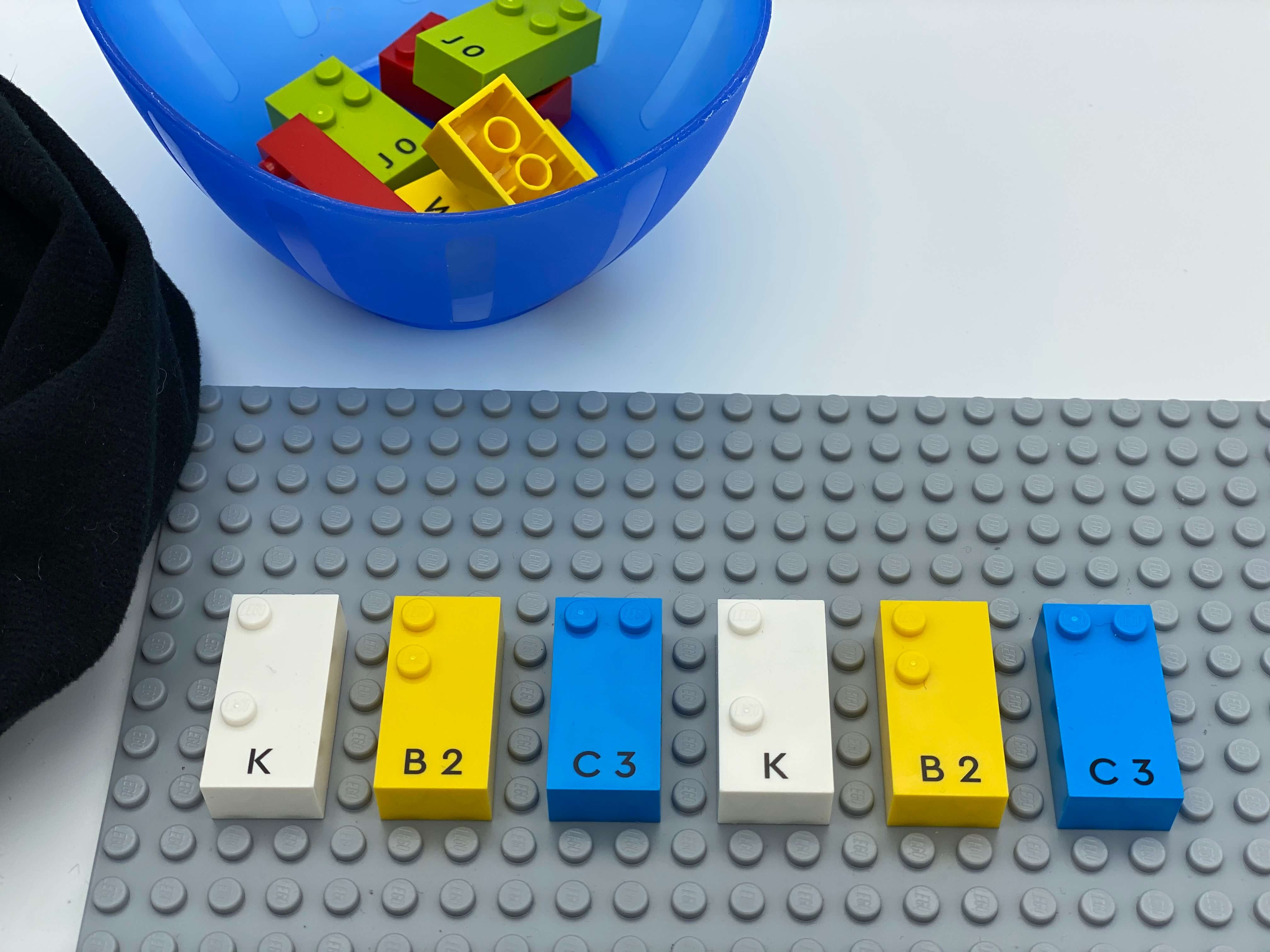 Letter bricks with 2 studs k, b, c, k, b, c aligned on the base plate, others bricks in the bowl.