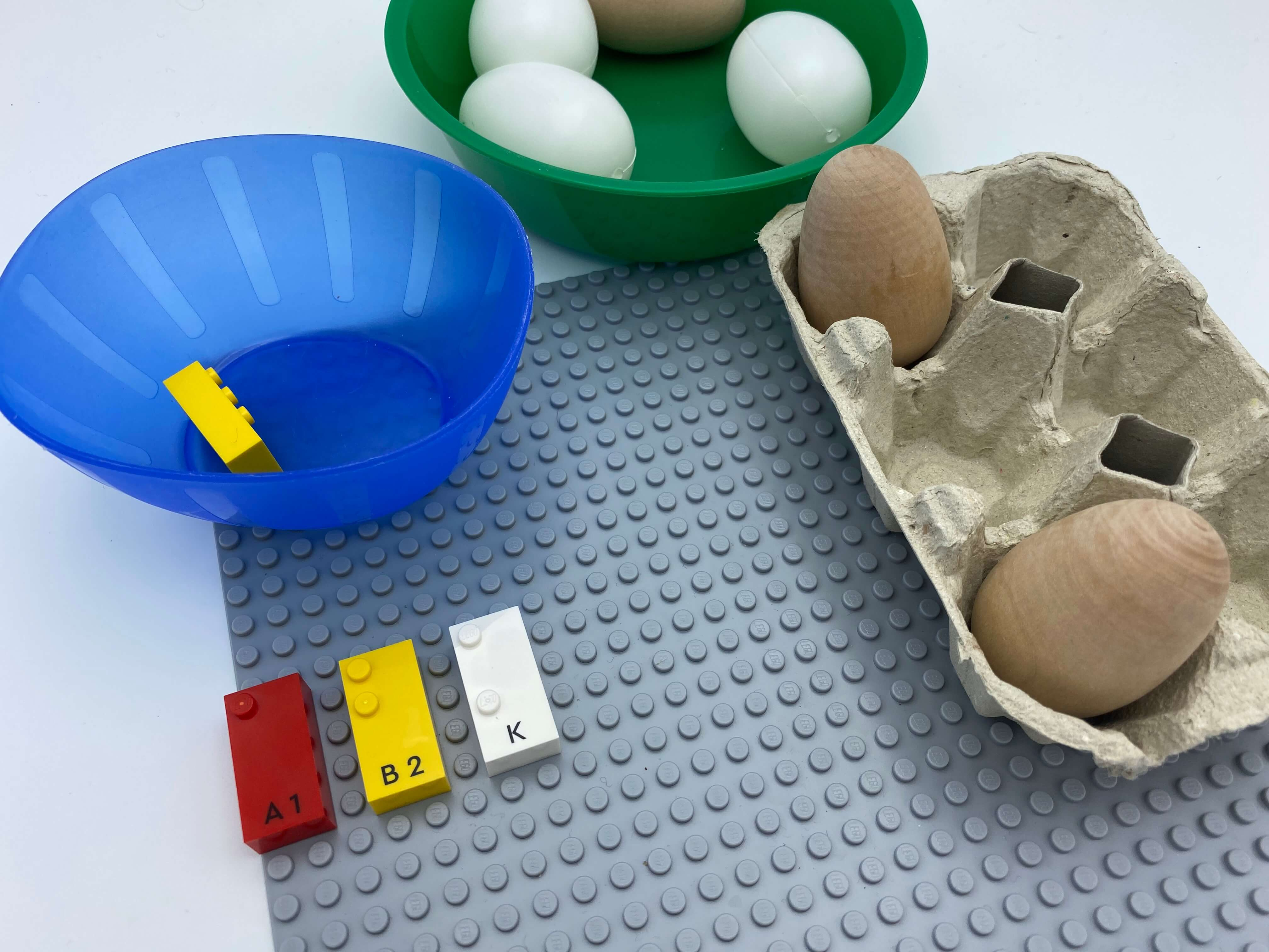 Letter brick k on the base plate, egg carton with 1 egg in dot 1 and in dot 3.