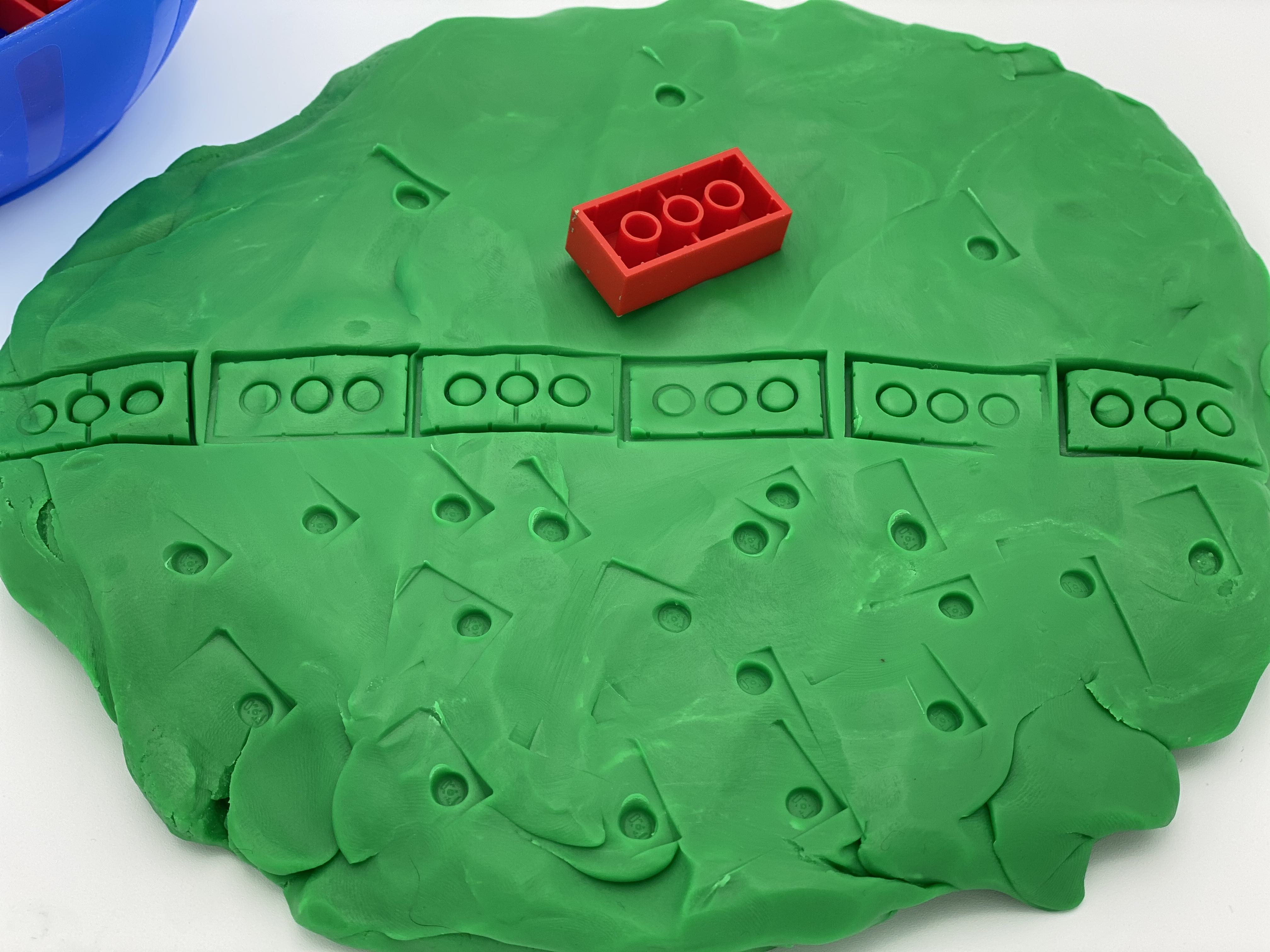 "A disk of playdough, prints with an ""a"" brick."