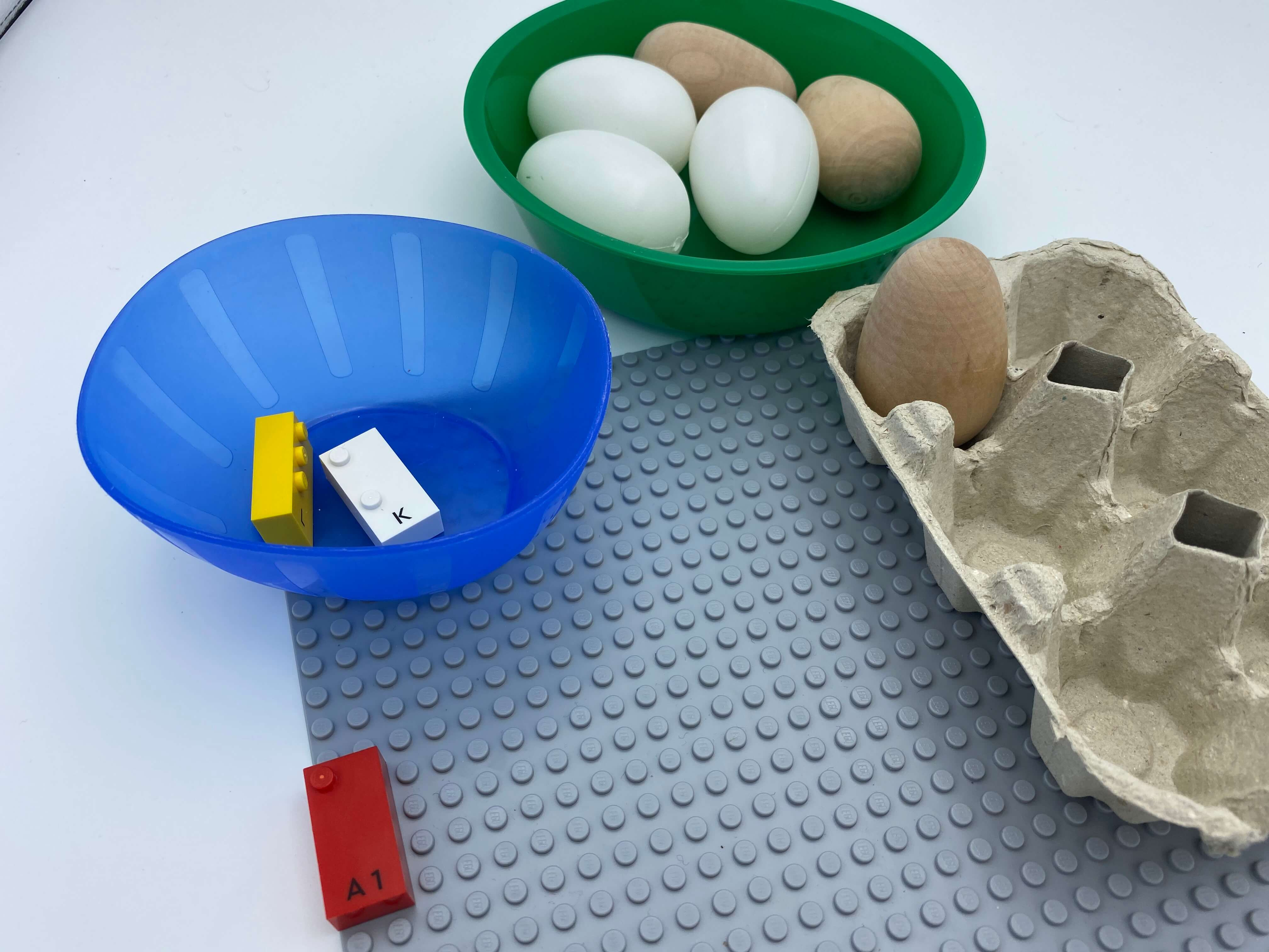 Letter brick a on the base plate, egg carton with 1 egg in dot 1, a bowl with 2 bricks, another bowl with 5 eggs.