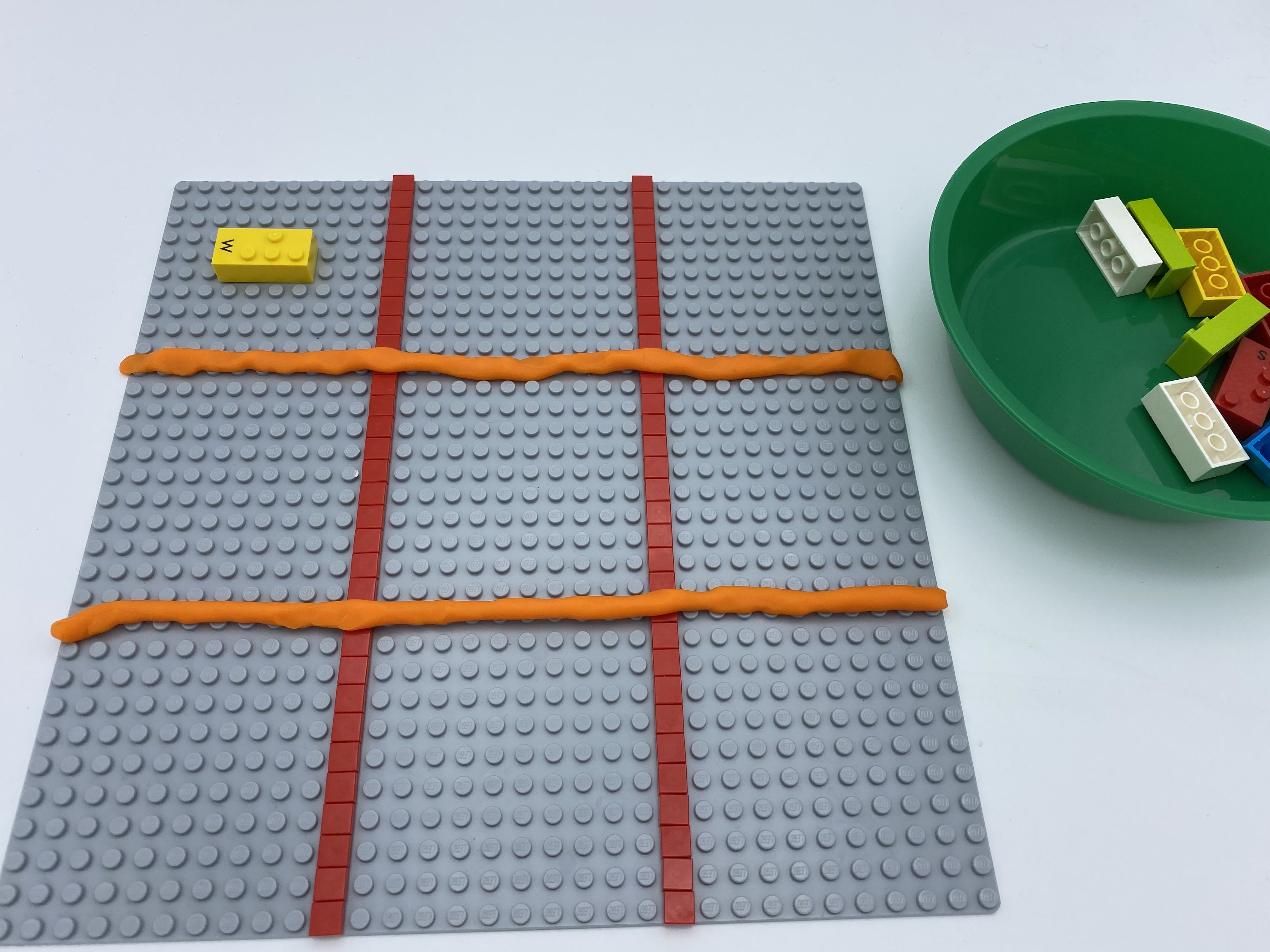 9 squares are made out of play-dough on a base plate. A horizontal bricks is attached in the top left square.
