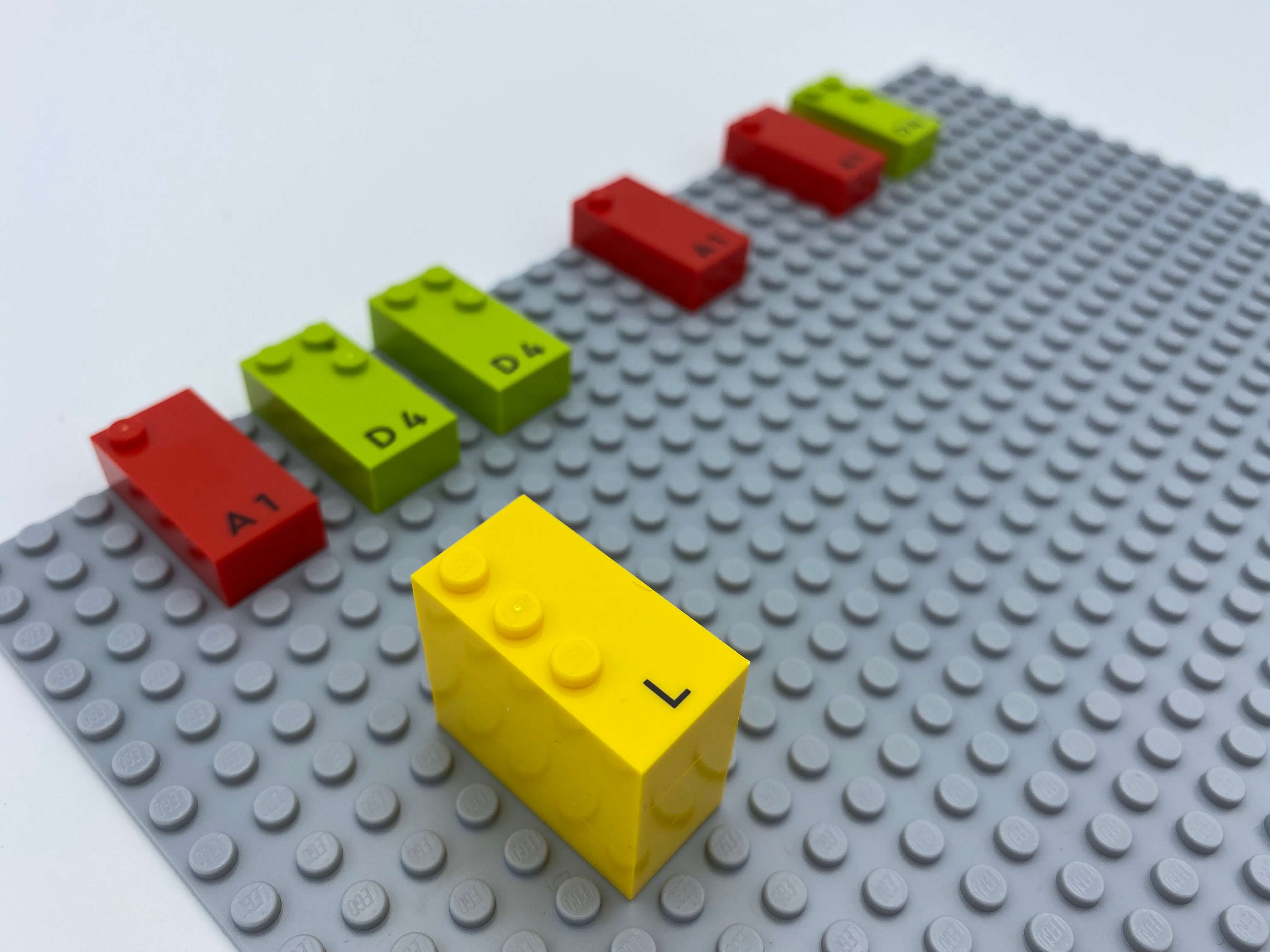 """Letter bricks aligned on the base plate: a mix of 3 """"a"""" and3  """"d"""", a tower of 3 letter bricks """"l""""."""